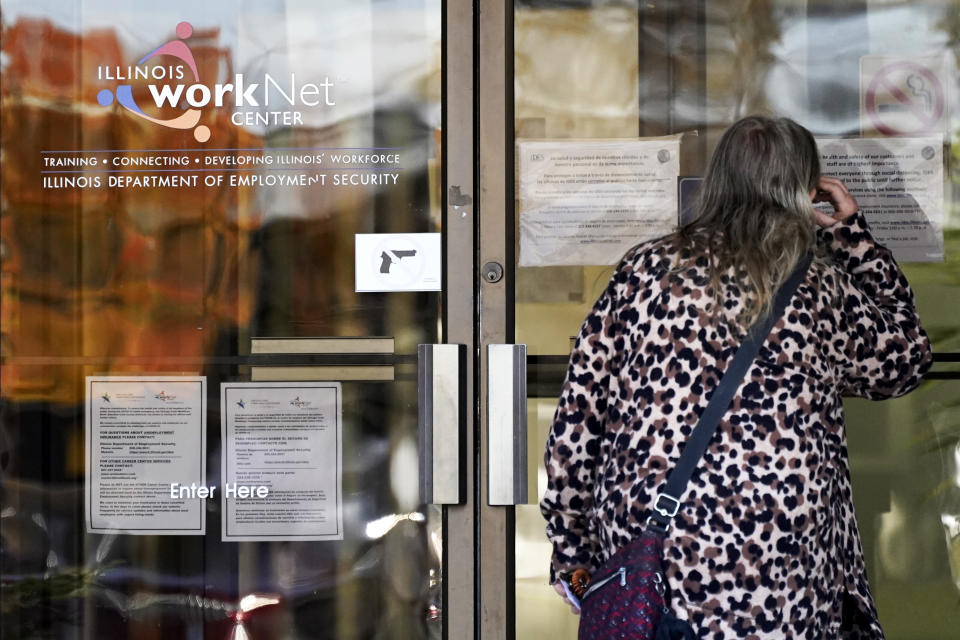 A woman checks information as information signs are displayed at IDES (Illinois Department of Employment Security) WorkNet center in Arlington Heights, Ill., Thursday, Nov. 5, 2020. Illinois reports biggest spike in unemployment claims of all states. (AP Photo/Nam Y. Huh)
