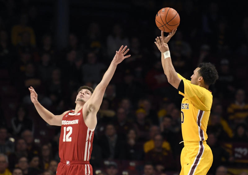Wisconsin's Trevor Anderson (12) guards against 3-point shot by Minnesota's Payton Willis (0) during the second half of an NCAA college basketball game Wednesday, Feb. 5, 2020, in Minneapolis. Minnesota won 70-52. (AP Photo/Hannah Foslien)