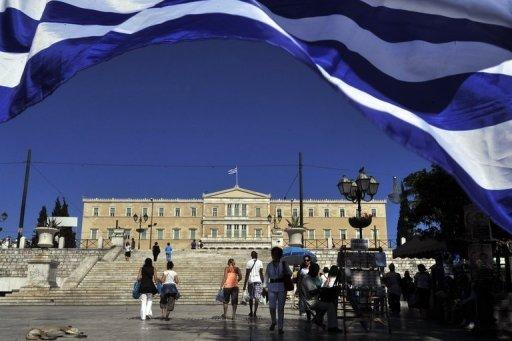 People walk at a central Athens square in front of the Greek parliament on May 16
