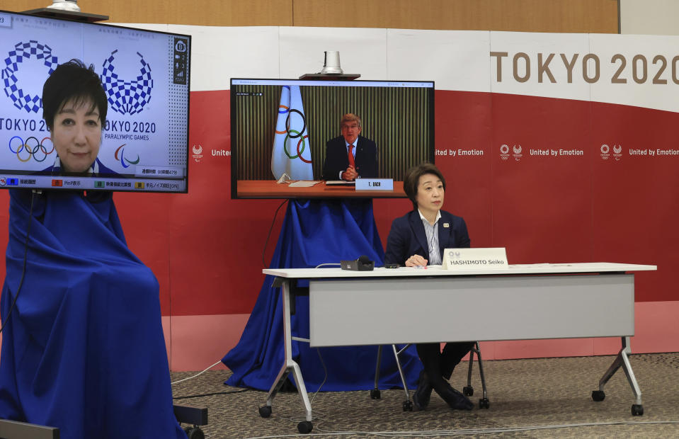 International Olympic Committee (IOC) President Thomas Bach, on a screen, delivers an opening speech while Tokyo 2020 Organizing Committee president Seiko Hashimoto and Tokyo Governor Yuriko Koike, left, listen at a five-party meeting of Tokyo 2020 Olympic and Paralympic Games with International Paralympic Committee (IPC) President Andrew Parsons and Japanese Olympic Minister Tamayo Marukawa in Tokyo Saturday, March 20, 2021. (Yoshikazu Tsuno/Pool Photo via AP)
