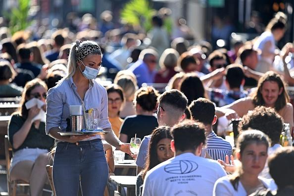 A waitress wearing a protective face covering brings drinks to customers in the late summer sunshine at outside tables in Soho, central London.
