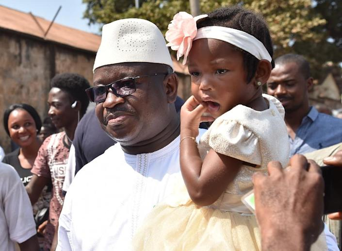 Julius Mada Bio, the candidate for the Sierra Leone People's Party, was accompanied by his daughter to the polling station (AFP Photo/ISSOUF SANOGO)