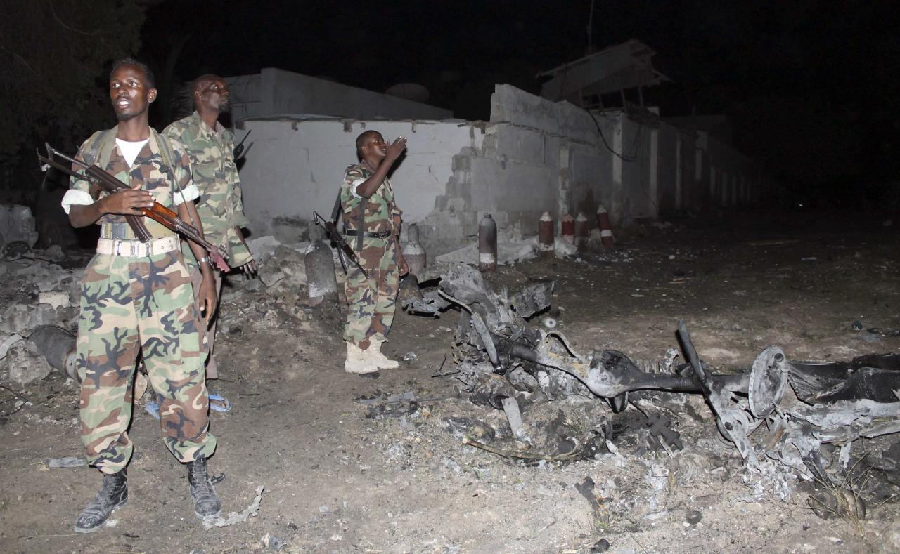 Soldiers assess the scene of an explosion outside the Jazira hotel in Mogadishu, January 1, 2014. Three bombs exploded within an hour outside the hotel in a heavily fortified district of the Somali capital on Wednesday, killing at least 11 people. REUTERS/Feisal Omar (SOMALIA - Tags: CIVIL UNREST CRIME LAW MILITARY)