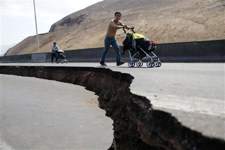 Residents push prams along a damaged road leading to Alto Hospicio commune after a series of aftershocks in the northern port of Iquique April 3, 2014. REUTERS/Ivan Alvarado