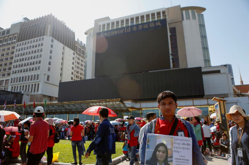 A cambodian worker holds up a placard during a protest for higher pay and better working conditions in front of the NagaWorld hotel and casino complex in Phnom Penh