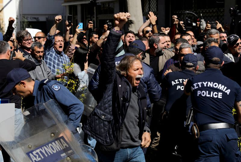 Turkish Cypriots shout slogans at the Ledra checkpoint of the U.N.-controlled buffer zone, after authorities declared the crossing temporarily shut to curb any potential spread of coronavirus, in Nicosia