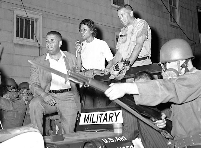 FILE - In this May 11, 1964, file photo, masked National Guardsman with their bayonets held at the ready surround the jeep of Brig. Gen. George Gelson, head of the guard unit, as Stanley Branche, chairman of the Committee for Freedom Now, left, and Gloria Richardson, second from left, stands beside him in Cambridge, Md. Richardson, an influential yet largely unsung civil rights pioneer whose determination not to back down while protesting racial inequality was captured in a photograph as she pushed away the bayonet of a National Guardsman, died Thursday, July 15, 2021, in New York, according to Joe Orange, her son in law. She was 99. (AP Photo/William Smith, File)