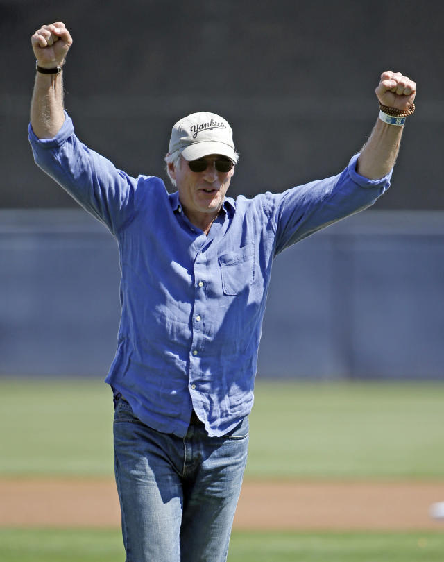 Actor Richard Gere reacts after throwing out the ceremonial first pitch for a spring training baseball game between the Tampa Bay Rays and the New York Yankees in Tampa, Fla., Sunday, March 9, 2014. (AP Photo/Kathy Willens)
