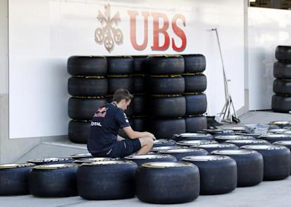 A Red Bull Formula One mechanic checks air pressures of tyres in front of a Swiss bank UBS sign at the pit lane at the Suzuka circuit