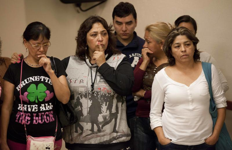 Family members of youth who disappeared in May from a Mexico City nightclub listen to prosecutor Rodolfo Rios at a press conference regarding a mass grave that was found in Mexico City, Thursday, Aug. 22, 2013. At least seven badly decomposed corpses have been recovered so far from a grave in Tlalmanalco, according to Rios. He said the victims can't be identified so far based on clothing, nor can they tell the cause of death. (AP Photo/Eduardo Verdugo)