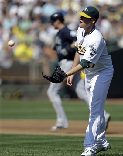 Oakland Athletics' Dan Straily, right, waits for a new ball as Seattle Mariners' Michael Saunders, background, runs the bases after hitting a two-run home run off Straily in the fourth inning of a baseball game Saturday, Sept. 29, 2012, in Oakland, Calif. (AP Photo/Ben Margot)