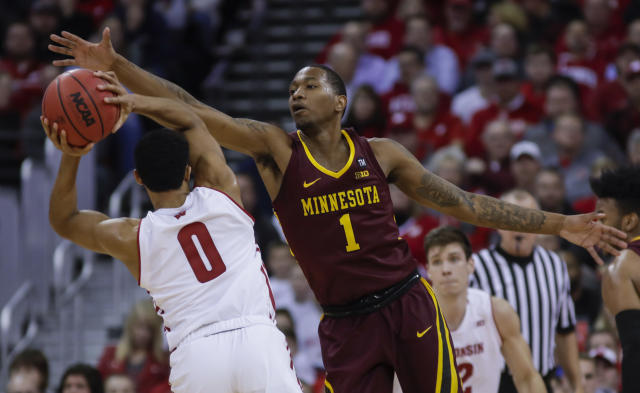 Minnesota's Dupree McBrayer (1) reaches for the ball held by Wisconsin's D'Mitrik Trice (0) during the first half of an NCAA college basketball game Thursday, Jan. 3, 2019, in Madison, Wis. (AP Photo/Andy Manis)