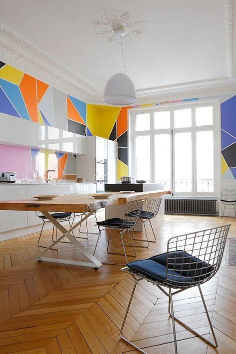 <p>This custom-painted wall animates and contemporizes the Neoclassical Parisian kitchen designed by Studio Razavi. The Bertoia chairs and shiny white cabinets bring a more streamlined, modern look while the raw wood table and herringbone hardwood floors chill things out. <br></p>