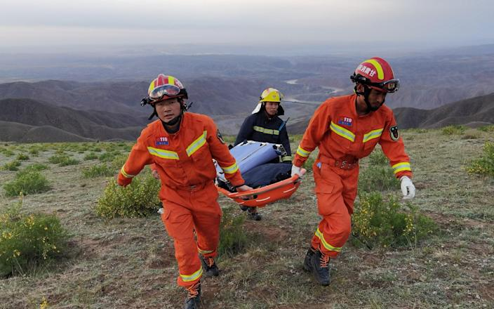 Rescue workers carry a stretcher as they work at the site where extreme weather killed participants of an ultramarathon in Baiyin, Gansu province, China - VIA REUTERS
