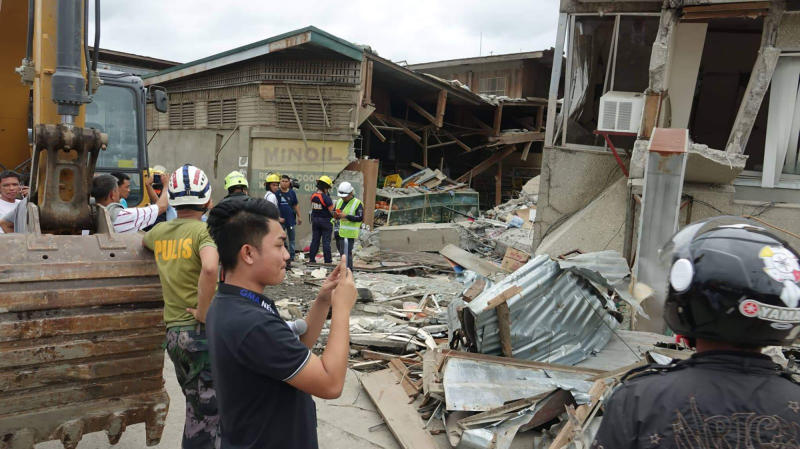 Residents and rescuers check damaged structures following an earthquake that struck Padada, Davao del Sur province, southern Philippines on Sunday Dec. 15, 2019. A strong quake jolted the southern Philippines on Sunday, causing a three-story building to collapse and prompting people to rush out of shopping malls, houses and other buildings in panic, officials said. (AP Photo)