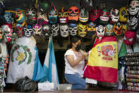 FILE - In this June 8, 2021, file photo, clerk Wendy Ramirez uses a Spanish flag to wrap souvenirs while preparing to close the store for the day on Olvera Street in Los Angeles. Los Angeles County residents are again required to wear masks indoors regardless of their vaccination status, a new mandate starting this weekend that health officials hope will reverse the latest spikes in coronavirus cases, hospitalizations and deaths. The rule went into effect late Saturday, July 17, for the nation's largest county, home to 11 million people, where a sharp increase in COVID-19 cases is led by the highly transmissible delta variant. (AP Photo/Jae C. Hong, File)