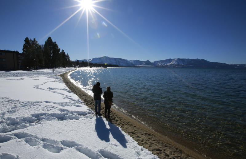 FILE - In this March 5, 2018 file photo, sunlight shimmers off the snow and waters of Lake Tahoe in South Lake Tahoe, Calif. Water stored at Lake Tahoe has nearly reached its legal limit after snowmelt from a stormy winter left behind enough to potentially last through up to three summers of drought. The lake has been within an inch of its maximum allowed surface elevation of 6,229.1 feet above sea level for more than three weeks and crept to within a half-inch this week. (AP Photo/Rich Pedroncelli, File)