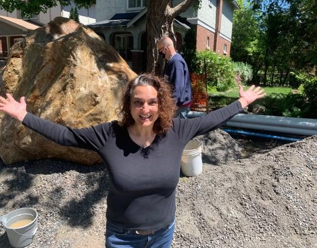 Gauri Sreenivasan stands in front of a massive boulder pulled out from beneath Bellwood Avenue during recent infrastructure work. It's believed the boulder is a glacial erratic, deposited there some 10,000 years ago. (Natalia Goodwin/CBC  - image credit)