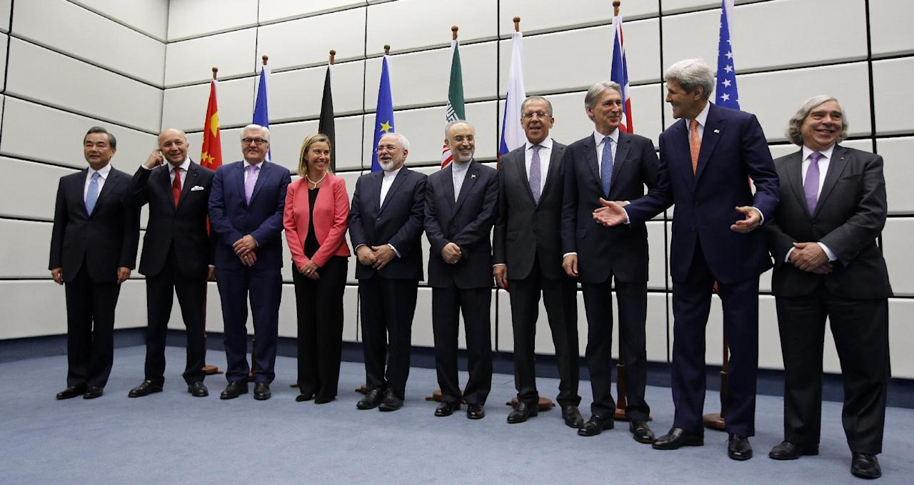 From left to right, Chinese Foreign Minister Wang Yi, French Foreign Minister Laurent Fabius, German Foreign Minister Frank Walter Steinmeier, European Union High Representative for Foreign Affairs and Security Policy Federica Mogherini, Iranian Foreign Minister Mohammad Javad Zarif, Head of the Iranian Atomic Energy Organization Ali Akbar Salehi, Russian Foreign Minister Sergey Lavrov, British Foreign Secretary Philip Hammon, U.S. Secretary of State John Kerry and U.S. Secretary of Energy Ernest Moniz pose for a group picture at the United Nations building in Vienna, Austria, Tuesday, July 14, 2015. After 18 days of intense and often fractious negotiation, world powers and Iran struck a landmark deal Tuesday to curb Iran's nuclear program in exchange for billions of dollars in relief from international sanctions — an agreement designed to avert the threat of a nuclear-armed Iran and another U.S. military intervention in the Muslim world. (Carlos Barria, Pool Photo via AP)
