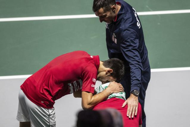 Serbia's Novak Djokovic, left, and captain Nenad Zimonjic, right, comfort teammate Viktor Troicki after losing the Davis Cup quarterfinal doubles match against Russia's Karen Khachanov, right, and Andrey Rublev in Madrid, Spain, Friday, Nov. 22, 2019. (AP Photo/Bernat Armangue)