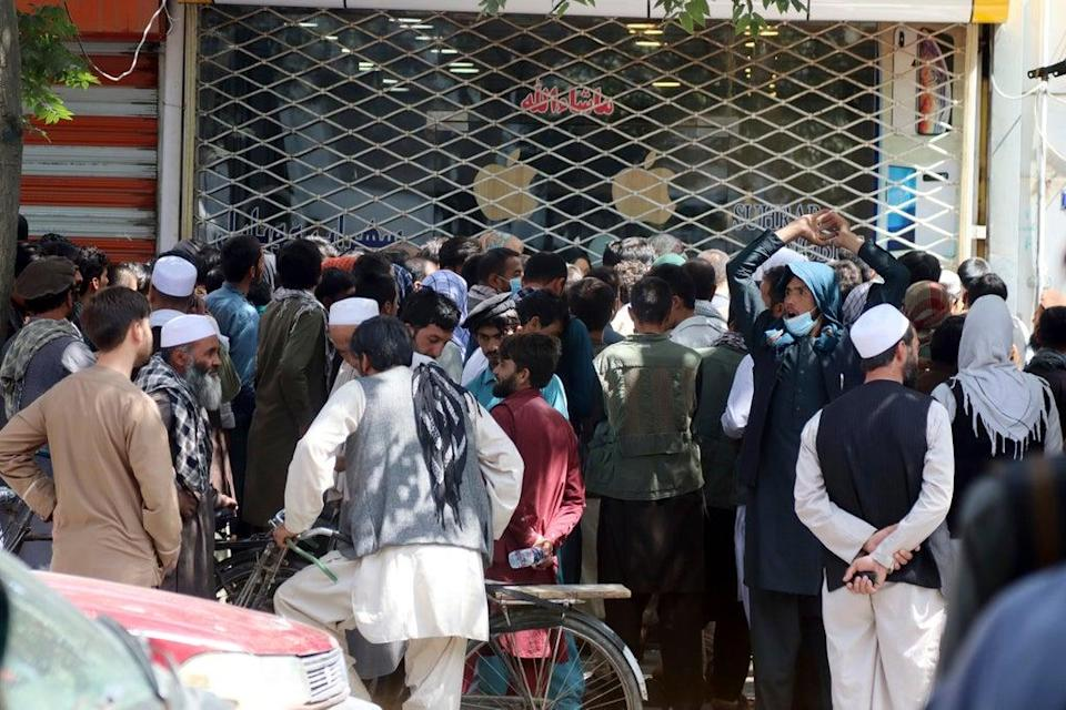 Afghans in front of New Kabul Bank having to wait for hours to try to withdraw money (AP)