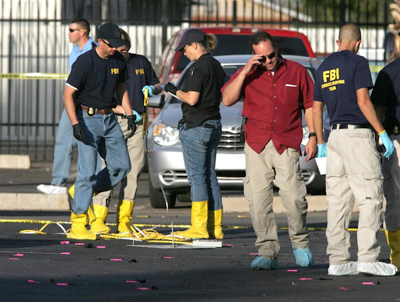 Federal agents investigate an apparent bomb explosion at the Social Security Administration office on Marshall Street in downtown Casa Grande, Ariz. on Friday, Nov. 30, 2012. No one was hurt in the explosion. (AP Photo/Casa Grande Dispatch, Oscar Perez)