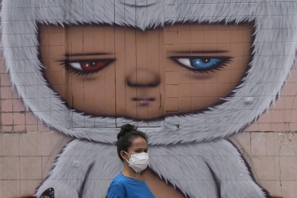 A woman wearing a face mask to help curb the spread the coronavirus walks past wall art in Bangkok, Thailand, Tuesday, July 20, 2021. (AP Photo/Sakchai Lalit)