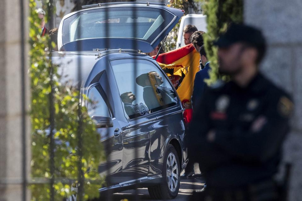Relatives of late dictator Gen. Francisco Franco hold a pre-constitutional Spanish flag at Mingorrubio's cemetery, outskirts of Madrid, Thursday, Oct. 24, 2019. Spain has exhumed the remains of Spanish dictator Gen. Francisco Franco from his grandiose mausoleum outside Madrid and flown them by helicopter for reburial in a small family crypt north of the capital. The government-ordered, closed-door operation on Thursday satisfies a decades-old desire of many in Spain who considered the vainglorious mausoleum that Franco built an affront to the tens of thousands who died in Spain's Civil War and his subsequent regime as well as to Spain's standing as a modern democratic state. (AP Photo/Bernat Armangue)