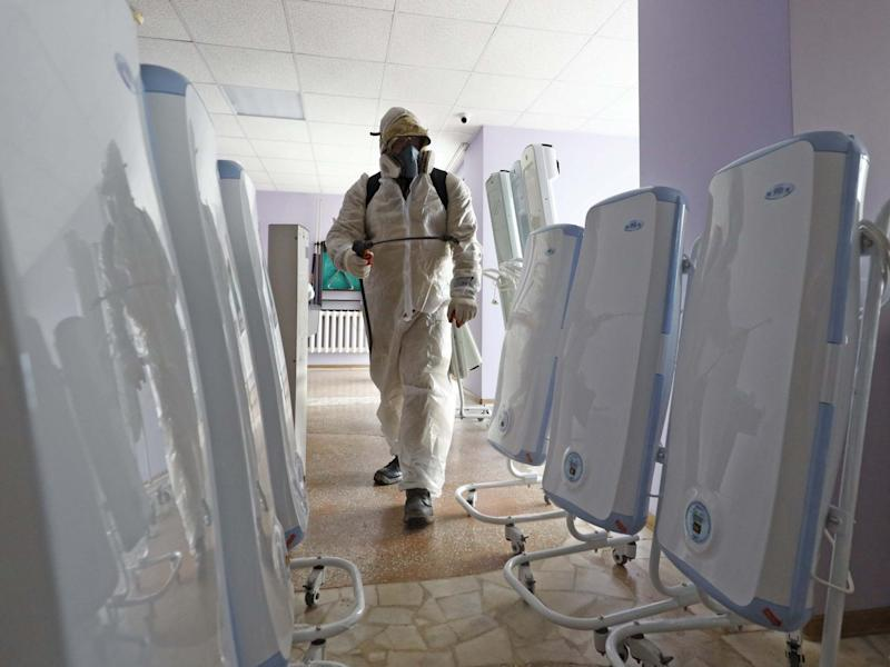 A worker in a chemical suit sprays disinfectant in a quarantine facility at the Gradostroitel health resort near the city of Tyumen after a 14-day quarantine for Russian nationals who were evacuated from Wuhan: Maxim Slutsky/TASS