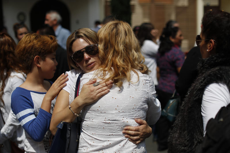 Angelica Macias Diaz, second left, who lost her son Raul Alexis Vargas, 7, is comforted by other relatives of the students and faculty who were killed when a building collapsed at the Enrique Rebsamen school during the 2017 earthquake embrace following a Catholic Mass next to the remains of the school, in southern Mexico City, Thursday, Sept. 19, 2019. Mexico was marking Thursday the Sept. 19 anniversaries of the 2017 earthquake that killed more than 300 people and a devastating 1985 temblor that left at least 9,500 dead.(AP Photo/Rebecca Blackwell)