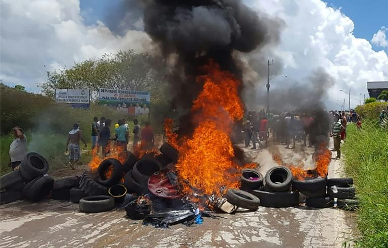 Residents of Pacaraima burn tires and the belongings of Venezuelan immigrants after attacking their two main makeshift camps, leading them to cross the border back into their home country on August 18, 2018