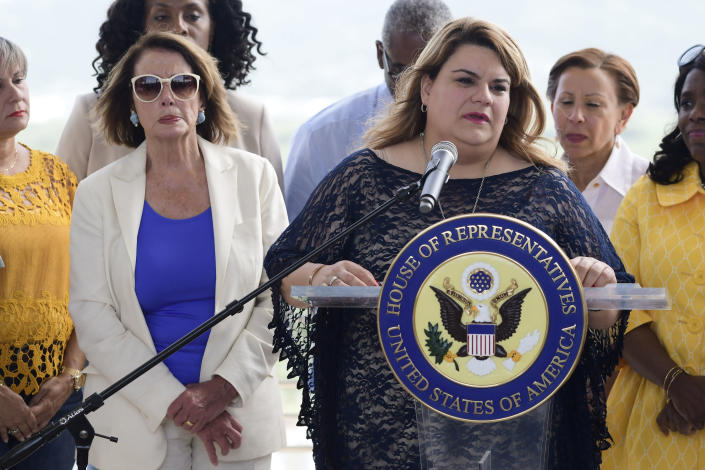 Resident commissioner Jennifer Gonzalez speaks at a joint press conference with members of a Congressional delegation led by House Democratic Leader Nancy Pelosi, left, at the Roque Díaz Tizol School in Yabucoa, Puerto Rico, Friday, July 27, 2018. Pelosi is pledging to help speed up Puerto Rico's hurricane recovery process after a two-day visit to the U.S. territory. (AP Photo/Carlos Giusti)