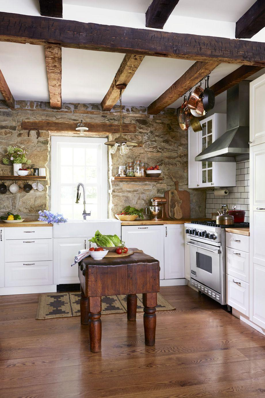 <p>With its dreamy stone wall, these homeowners brought in white cabinets, countertops, and a huge apron-front sink (all from Ikea). The adjacent wall is covered in classic white subway tile with dark gray grout, which lends a graphic, modern touch to the otherwise rustic space.</p>