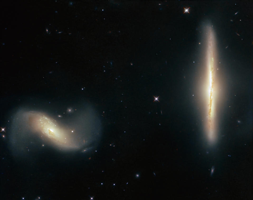 "While it's common for galaxies to coexist peacefully in the same cosmic neighborhood, these two galaxies are a bit too close for comfort. The galaxies NGC 6286 (right) and NGC 6285 (left), collectively known as Arp 293, are tugging at each other with their mutually strong gravitational attraction, dragging wisps of gas and dust out from the galaxies and into interstellar space. This causes the galaxies to appear ""smudged"" and blurred from our perspective on Earth. The Hubble Space Telescope captured this image of the galactic pair, which are located more than over 250 million light-years from Earth in the constellation Draco."