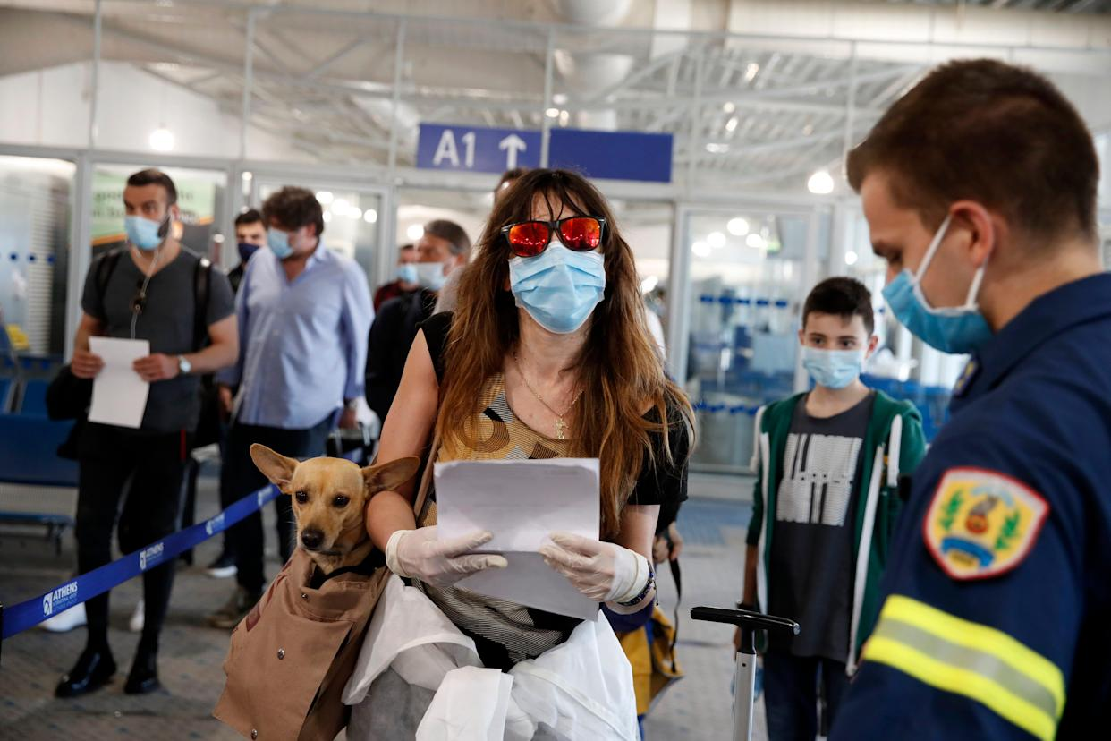 """A firefighter directs passengers who arrived to the Eleftherios Venizelos International Airport in Athens, Monday, June 15, 2020. The Centers for Disease Control recently moved Greece to its """"Level 4: COVID-19 Very High"""" travel advisory category."""