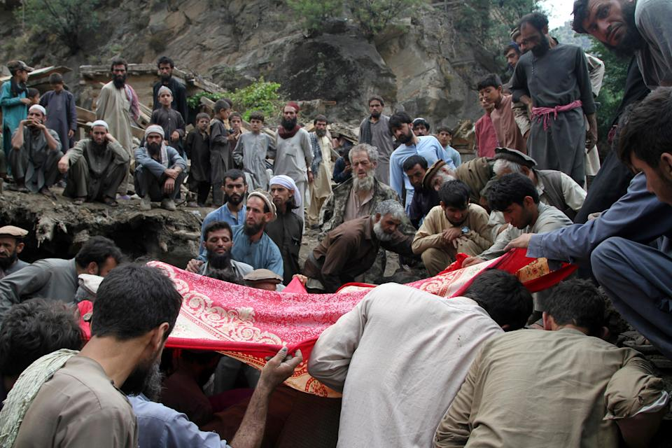 Locals search for victims of a mudslide following heavy flooding in Nuristan (AP)