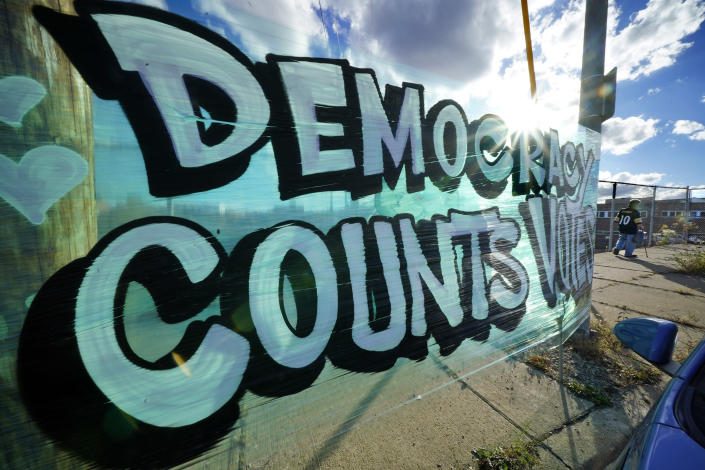 A sign saying Democracy Counts Votes hangs near the Allegheny County Election Division Warehouse on Pittsburgh's Northside where votes continue to be counted, Tuesday, Nov. 10, 2020. (AP Photo/Gene J. Puskar)