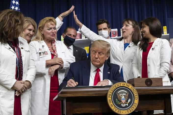 """Supporters celebrate as President Trump signs an executive order on lowering drug prices on Friday. <span class=""""copyright"""">(Alex Brandon / Associated Press)</span>"""