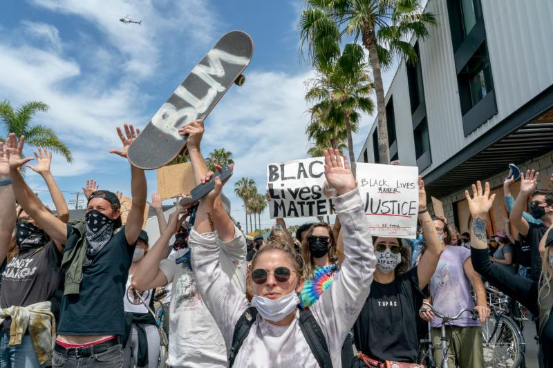 Protestors hold their hands up and march during a demonstration over the death of George Floyd in the Venice area of Los Angeles on June 2, 2020. - Anti-racism protests have put several US cities under curfew to suppress rioting, following the death of George Floyd in police custody. (Photo by Kyle Grillot / AFP) (Photo by KYLE GRILLOT/AFP via Getty Images)