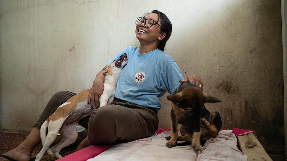 Dog rescuer Rathany Tan smiles as she plays with two young dogs.