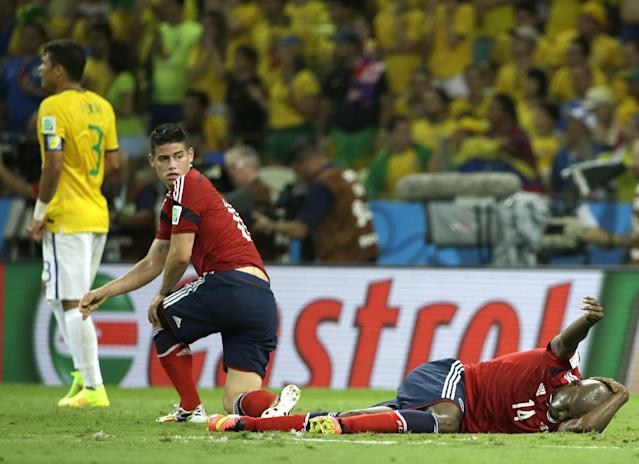 Colombia's Victor Ibarbo grimaces after being hit in the head as Colombia's James Rodriguez looks on during the World Cup quarterfinal soccer match between Brazil and Colombia at the Arena Castelao in Fortaleza, Brazil, Friday, July 4, 2014. (AP Photo/Hassan Ammar)