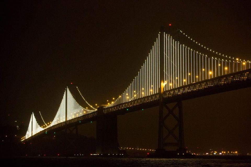 """<p>The San Francisco Bay Area is lucky enough to have two internationally renowned bridges. The newer <a href=""""https://www.popularmechanics.com/technology/infrastructure/a9396/how-they-built-the-record-setting-new-bay-bridge-span-15859172/"""" rel=""""nofollow noopener"""" target=""""_blank"""" data-ylk=""""slk:Bay Bridge East Span"""" class=""""link rapid-noclick-resp"""">Bay Bridge East Span</a>, a $6.4 billion project, replaced a seismically unstable bridge. It has the world's longest self-anchored suspension span at 2,047-feet-long and is anchored by a single 525-foot-tall tower that holds a main cable containing 17,399 steel wire strands. The single 2.6-foot-diameter main cable loops around the roadway, held aloft the tower that supports 90 percent of the bridge's weight, giving engineers a solution to placing one of the world's widest bridges in the tricky soil conditions of the Bay Area.</p>"""