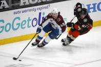 Colorado Avalanche defenseman Samuel Girard (49) works with the puck next to Anaheim Ducks forward Maxime Comtois (53) during the second period of an NHL hockey game in Anaheim, Calif., Friday, Jan. 22, 2021. (AP Photo/Ringo H.W. Chiu)