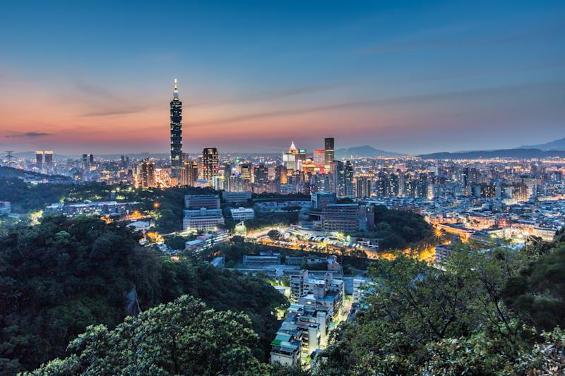 Sunset shot of Taipei 101 with orange glowing sky in the background while the city lights up.