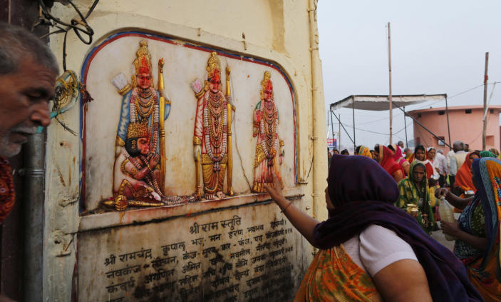 A Hindu pilgrim touches in obeisance an image of Hindu deities Rama, Sita and Lakshman in Ayodhya, India , Saturday, Nov. 9, 2019. India's security forces were on high alert ahead of the Supreme Court's verdict Saturday in a decades-old land title dispute between Muslims and Hindus over plans to build a Hindu temple on a site where Hindu hard-liners demolished a 16th century mosque in 1992, sparking deadly religious riots. (AP Photo/Rajesh Kumar Singh)
