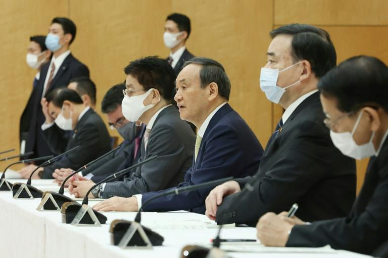 Japan's Prime Minister Yoshihide Suga (C) told a ministerial meeting that disposing of the water was an 'inevitable task'