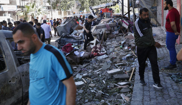 People inspect the rubble of destroyed the Abu Hussein building that was hit by an Israeli airstrike early morning, in Gaza City, Wednesday, May 19, 2021. (AP Photo/Adel Hana)