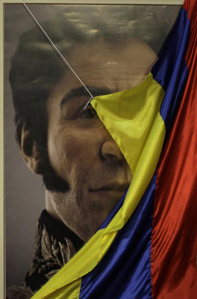 A Venezuelan flag drops to unveil a photograph-like portrait of Venezuela's independence hero Simon Bolivar during a ceremony marking the 229th anniversary of Bolivar's birth at Miraflores presidential palace in Caracas, Venezuela, Tuesday, July 24, 2012. A team of researchers produced the image based on studies of Bolivar's remains. (AP Photo/Fernando Llano)