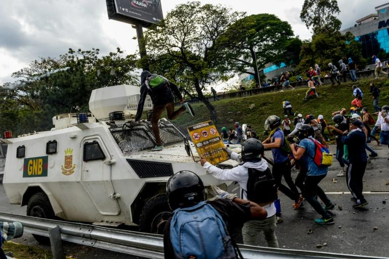 Venezuelan opposition activists confront a police armoured vehicle during a protest against President Nicolas Maduro, in Caracas, on May 1, 2017