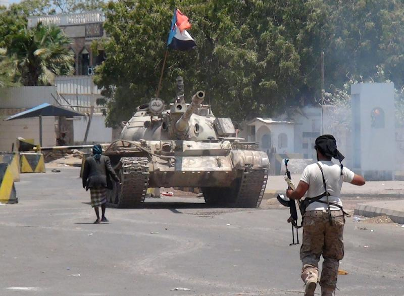 A Yemeni supporter of the southern separatist movement, walks in front of a tank bearing the movement's flag, which they confiscated from a military depot, in the southern Yemeni city of Aden on March 27, 2015 (AFP Photo/Saleh al-Obeidi)